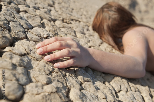 Woman lying on cracked land with focus on hand
