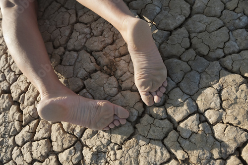 Low section of a woman lying on cracked land