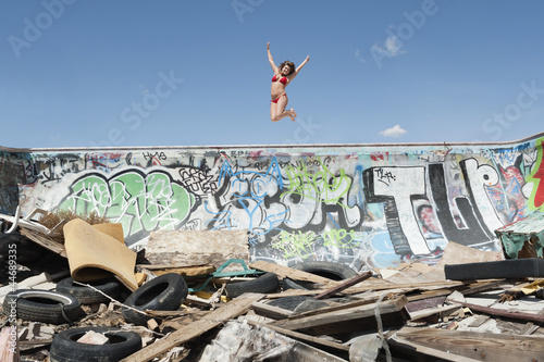 Young woman in bikini jumping over graffiti wall with garbage in foreground