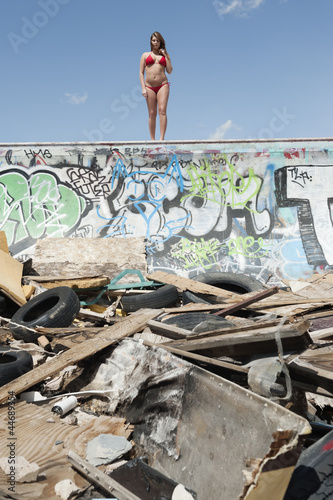 Young woman in bikini standing on graffiti wall with garbage in foreground