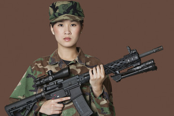Portrait of beautiful young US Marine Corps soldier with M4 assault rifle over brown background