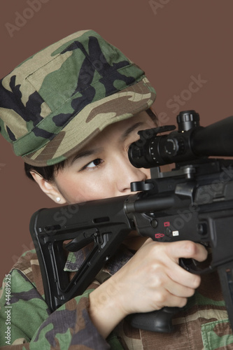 Young female US Marine Corps soldier aiming M4 assault rifle over brown background