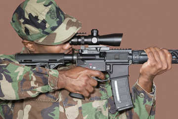 Male US Marine Corps soldier aiming M4 assault rifle over brown background