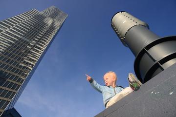 Kleiner Junge sitzt vor einem Schornstein vor blauem Himmel