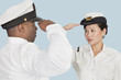Multi-ethnic US Navy officers saluting each other over light blue background