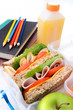 School books and healthy wholemeal sandwich with apple