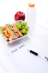 Healthy packed lunch with empty food diary copy space