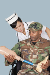 Nurse with US Marine Corps soldier holding artificial limb as he sits in wheelchair over light blue background
