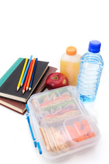 Healthy packed lunch for school with books and pencils