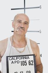Mug shot of senior gangster smoking cigarette