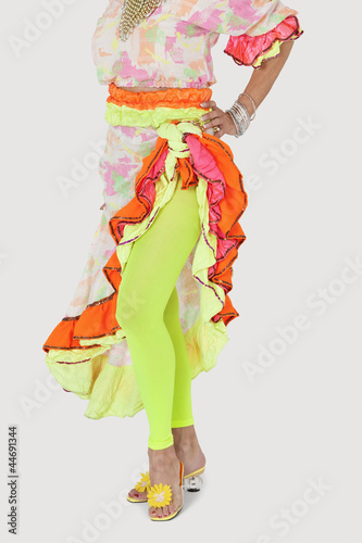 Low section of woman in Brazilian outfit with hand on hip over gray background