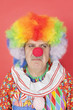 Senior male clown frowning over red background