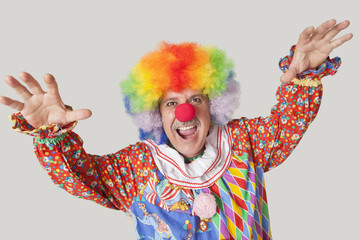 Portrait of funny clown with arms raised and mouth open against colored background