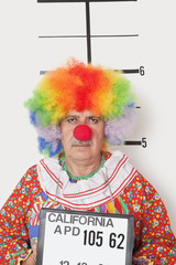 Portrait of senior clown posing for mug shot