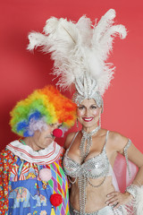Portrait of happy senior showgirl with sad clown standing against red background