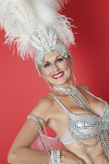 Portrait of happy senior showgirl with feather headpiece over red colored background