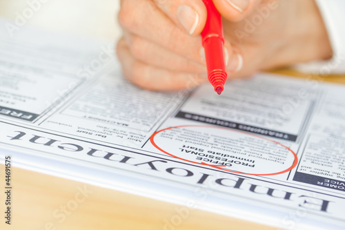 Hand with Red Pen Marking Job in Newspaper
