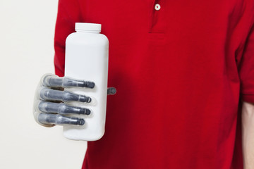 Mid section of a man holding bottle with prosthetic hand over gray background