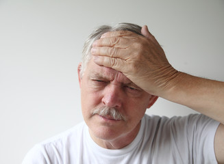 a man puts his hand to his forehead in pain