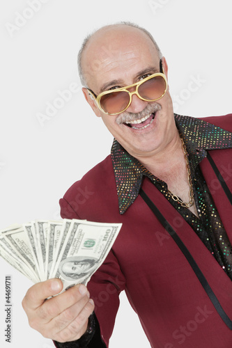 Portrait of happy senior man showing US banknotes against gray background