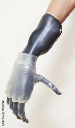 Close-up of man's prosthetic hand over gray background