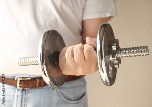 man holds a heavy weight in his hand