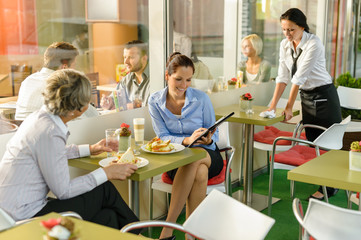 Businesswomen talking business in lunch break cafe