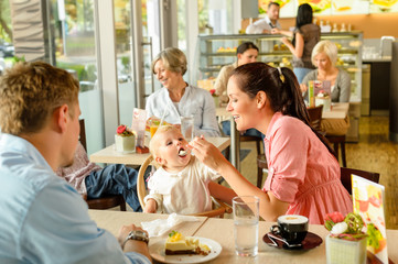 Father and mother feeding child cake cafe