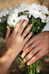 Hands with wedding rings on the bouquet
