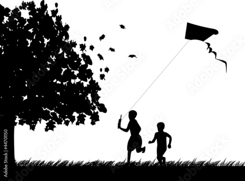 Silhouette of running boys with flying kite in autumn or fall