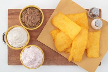 polenta fritta con salse su tavolo bianco