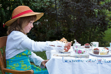 Beautiful little girl having a garden tea party