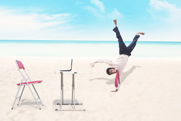 Businessman breakdancing at beach