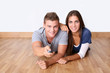 Cheerful young couple using tv remote control