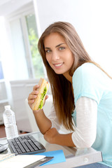 Student girl eating sandwich in front of desktop