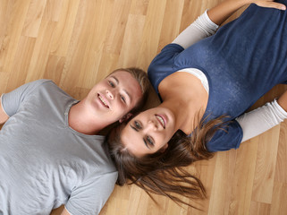 Upper view of young couple laying on the floor