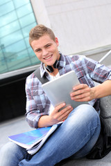 University student using digital tablet and headphones