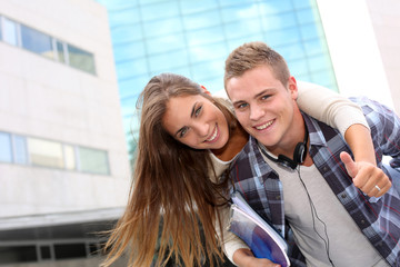Young guy giving piggyback ride to girlfriend