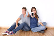 Teens showing mobile phones to camera