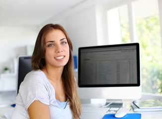 Young woman in office with desktop screen on background