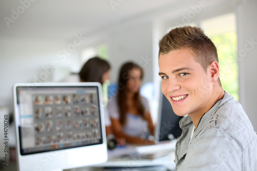 Young man sitting in office in front of desktop computer - 44708760