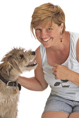 Smiling woman pets cute shaggy dog