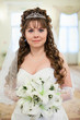 Pretty Caucasian bride in white dress and with lilies flowers