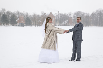 Newly married holding hands on freezing lake area in winter