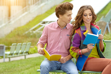 couple of students with  sitting at campus park and reading book