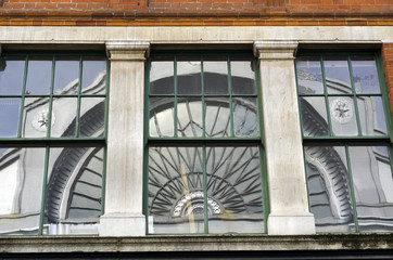 Arched window reflected in building glass