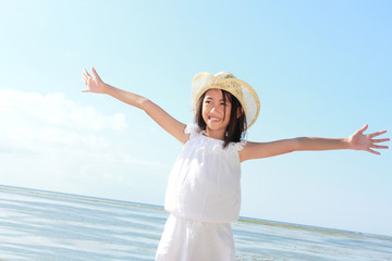 girl raises her hands against blue sky