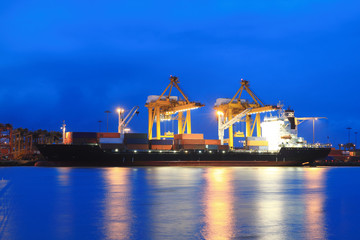 Containers loading at sea trading port at Twilight