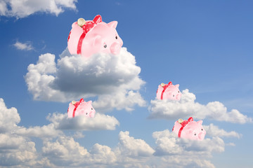 Pigs-coin boxes sit on white clouds in the blue sky