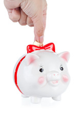 hand lowers a coin in a pig a-coin box